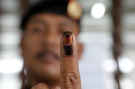 A Malaysian voter shows his finger marked with ink after casting his ballot during the early voting for the general elections in Kuala Lumpur