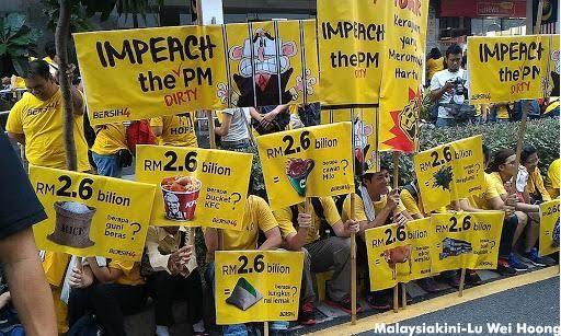 Wiele mówiące transparenty, pokazujące ileż to dóbr można by zakupić za te zdefraudowane 2,6 mld MYR.