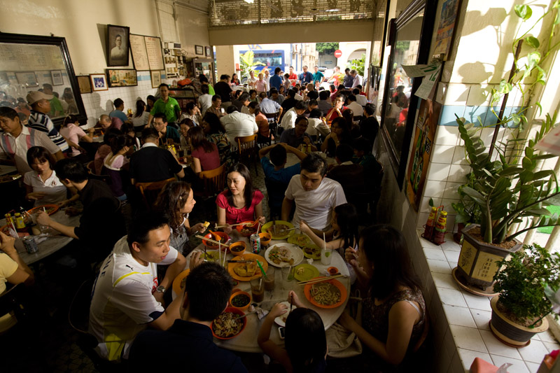 the busy dining room at yut kee with diners queing for tables at the entrance
